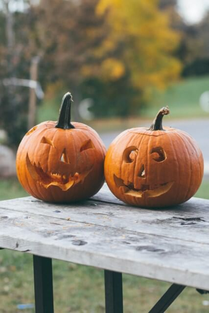 two jack-o-lanterns sitting on a table on the yard